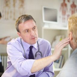 Male doctor looking an a patient's ear